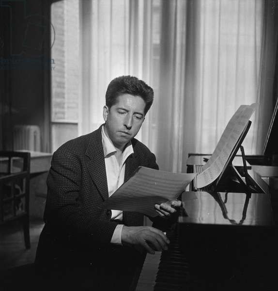 Henri Dutilleux at a piano, May 1958 (b/w photo)