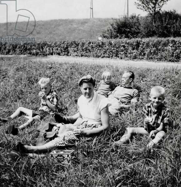 Family on a cycling holiday taking a rest along the road. Netherlands, 1950-70