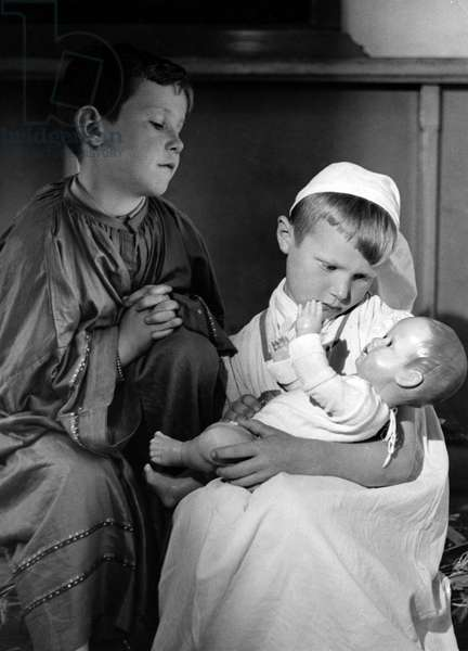 Two dressed up children play creche (Christmas figurines), The Netherlands, 1950