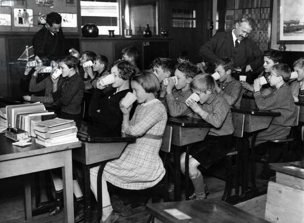 A school class in Kwadijk is drinking school milk for the first time, poured into mugs by the teacher, The Netherlands, January 1936