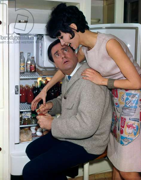 Man and woman in the door opening of a full refrigerator, Netherlands, February 1964 (photo)