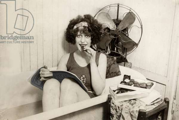 Heat, heat waves, dry monsoons. Due to the warm weather this young lady sits in a bath of ice water, a fan in her back, and she eats ice confectionery, while she reads a magazine 1925.