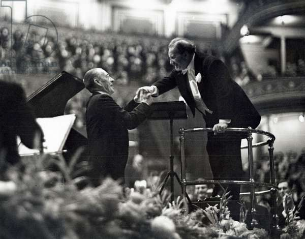The soloist behind the piano of the evening, Sergei Rachmaninoff congratulates the jubilating conductor Henry Wood of the London Orchestra in the Royal Albert Hall, London, October 6, 1938 (b/w photo)