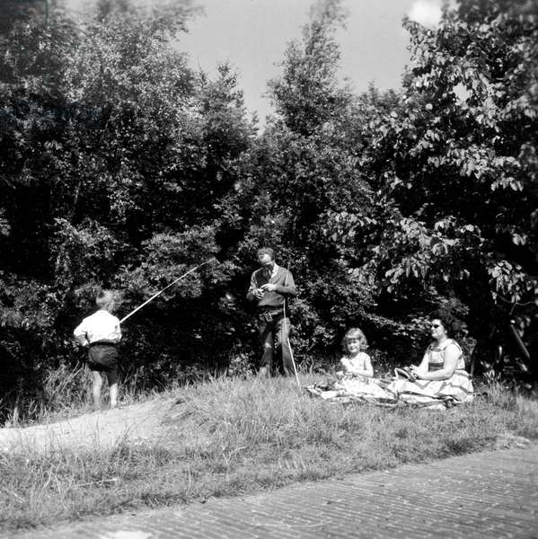Family along the waterfront. The man is baiting his fishingrod. Netherlands, August 1960