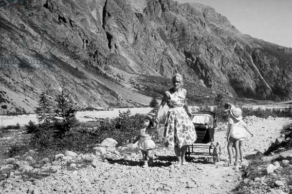 Holidays: Woman is dressed in floral dress and with three small children and a baby on a rocky path in the mountains