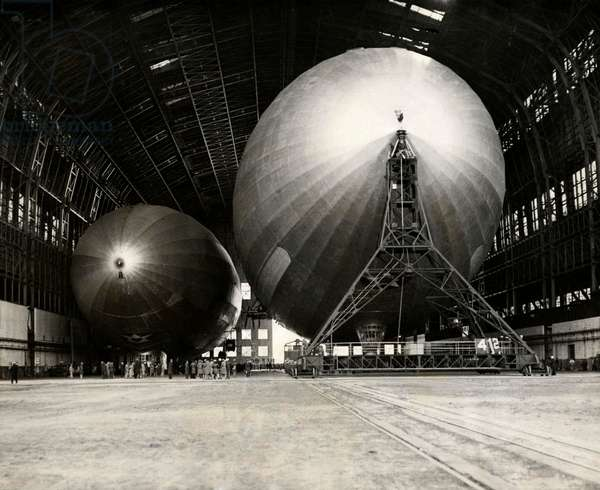 The American airship Akron next to the smaller Zeppelin Los Angeles in the hangar of marine air base Lakehurst, the United States of America, 22 October 1931 (b/w photo)