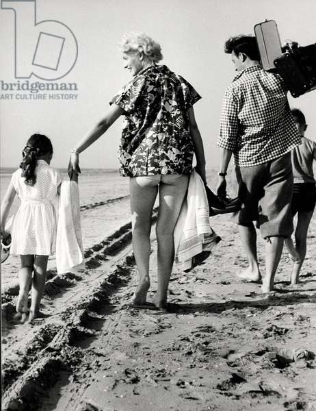 Father, mother and children walking barefoot along the tide line. Netherlands, 1950-1960