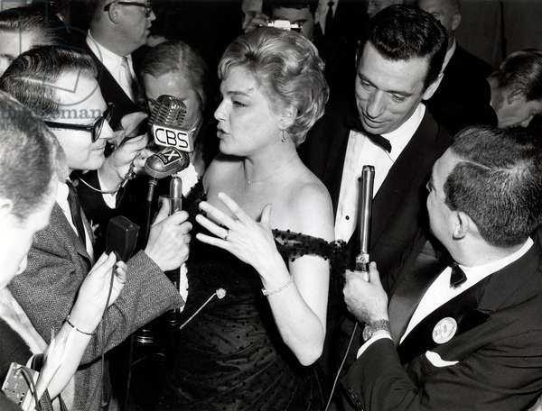 Simone Signoret and her husband Yves Montand, dressed in gala clothing, with a horde of journalists who are armed with many microphones, 1964 (b/w photo)