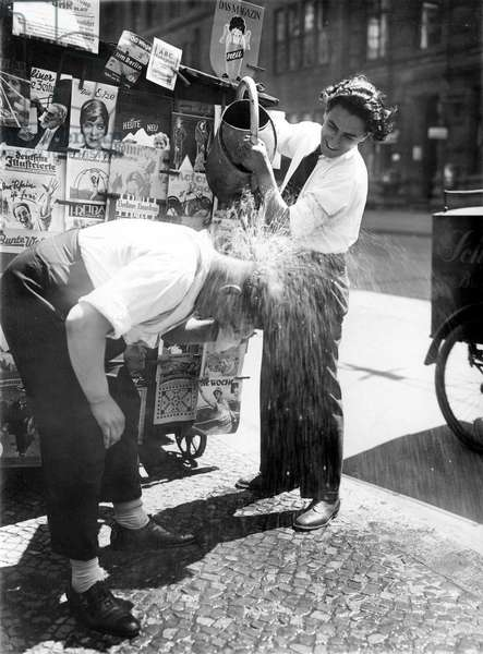 Heat. Magazines seller gets cool water poured over his head. Besides his newsstand with magazines, he bends over while another man pours water from a watering can. 07/03/1930, Berlin