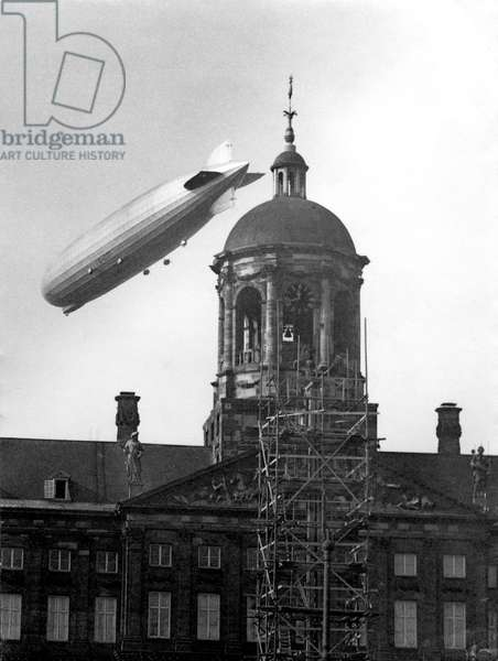 The airship Graf Zeppelin above the Dutch Royal Palace with a scaffold in front, seen from Amsterdam Dam at 11.43 am, The Netherlands, October 1929 (b/w photo)