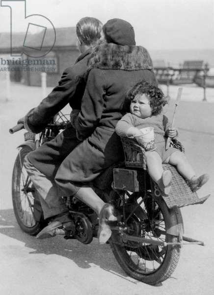 English family on the motor bike: father and mother, and child/baby in wicker seat backwards behind her mother, 1932