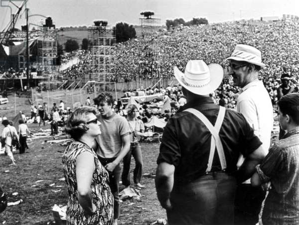 Man with cowboy hat surveys the crowd, Woodstock, USA, 1969 (b/w photo)