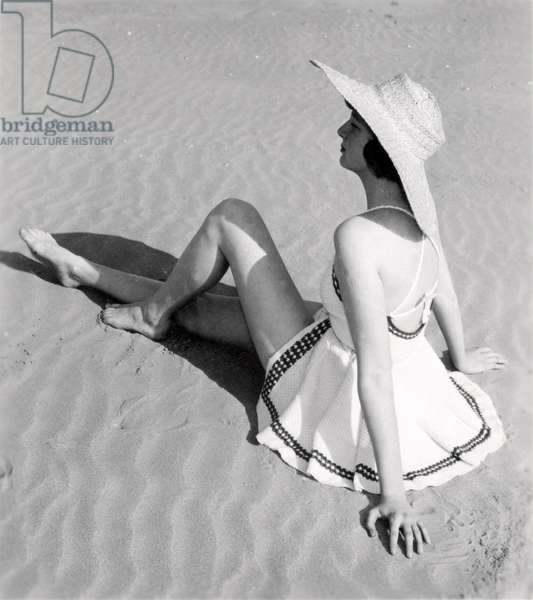Woman with hat in a knitted swimsuit, sunbathing on the beach. Date unknown