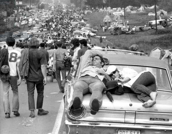 Couple sunbathing on the hood of a car, en route to Woodstock, USA, 1969 (b/w photo)