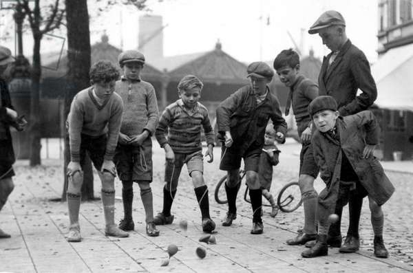 Children playing in the street with whipping tops. Belgium, around 1930