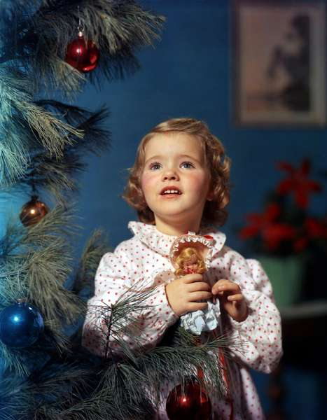 Girl in pajamas with doll next to a Christmas tree with Christmas balls