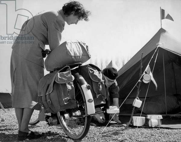 A couple on camping holiday with a moped and tent, 1953