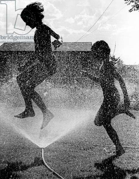 Heat. Two children trying to cool down in the summer heat. They jump through the water spray from a garden hose. Time and place unknown