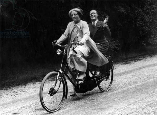 Prince Bernhard and Princess Juliana on a tandem-bicycle in the Palace gardens in The Hague 1936