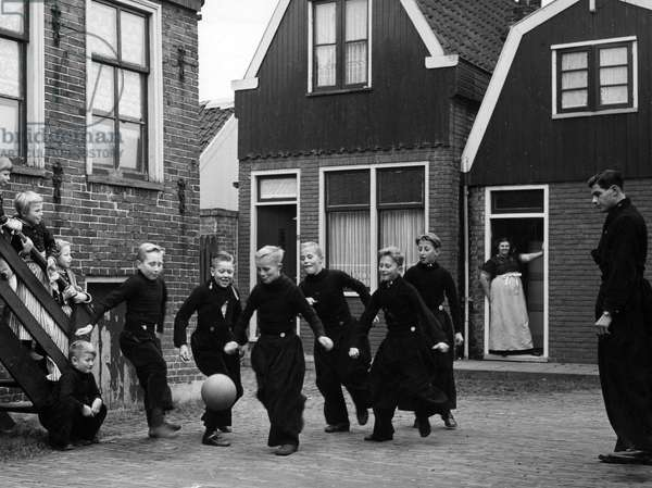 Boys in local costume, playing with a ball in the streets of a Dutch village, Holland, Volendam, 1958.