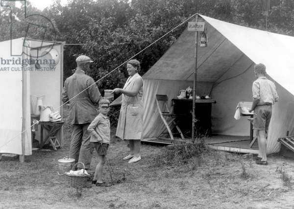Family near a half-open tent on camp site Bakkum, the Netherland), 1932