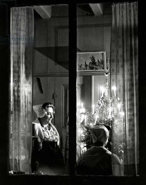 Women in traditional clothing from the province of Zeeland with a lighted Christmas tree, seen through the window. Ritthem, November 1949