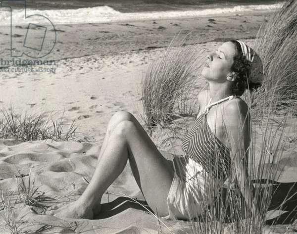 Women's fashion, swimwear, beachwear. Sunbathing woman in shorts and halter. Australia, 1926.