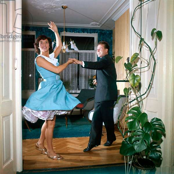 Man and woman dancing Rock and Roll in the living room between plants, Netherlands, 1960 (photo)