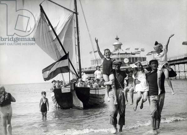 Boatmen bring children back to the beach at the pier, after a joy ride in their boat, summer 1939.