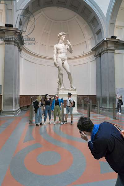 Taking a photo in front of the statue of David by Michelangelo,