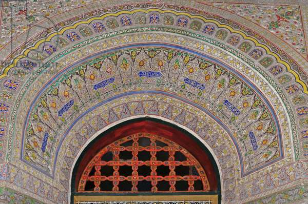Fes. Interior of Mnebhi Palace, early 20th cent. Islamic architecture. Decorated arch. Colourful mosaic. Floral patterns. Morocco