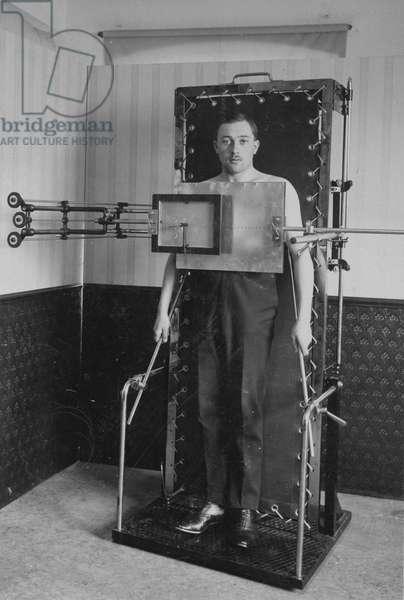 Man in an x-ray machine, 1921 (b/w photo)