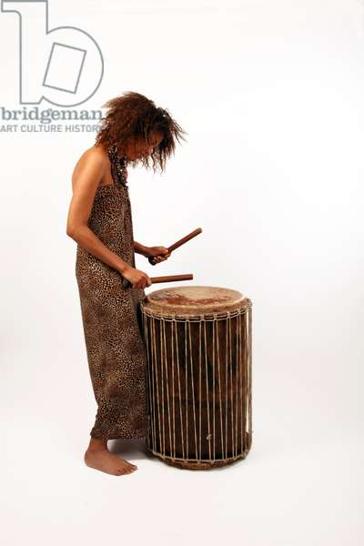 Young African woman playing a Doum Doum drum. A large African drum or percussion instrument made from a hollowed out wooden log and a natural hide or skin stretched over both ends and held in place with rope or twine  - generic