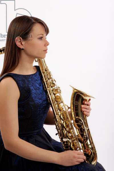 Young woman in a recital outfit holding a tenor saxophone