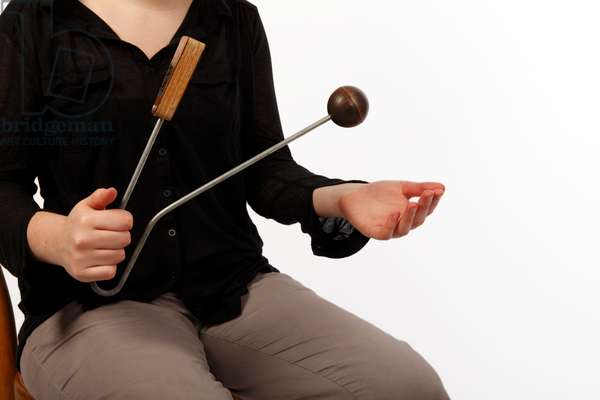 Vibraslap being played. Percussion sound effect instrument played by striking the wooden ball, making the metal teeth inside the wooden box rattle. Modern equivalent of the 'Jawbone of an Ass'