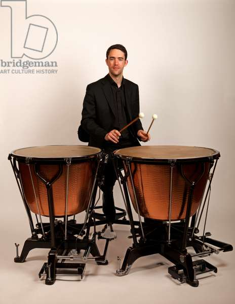 Timpanist playing two calf-headed Ringer style timpani.