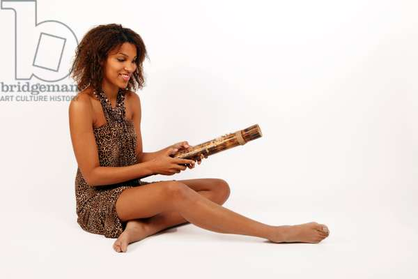 Young African woman playing a Valiha, Bamboo Zither or tube harp. Made from a short section of bamboo with metal strings running top to bottom around the whole of the tube, stretched over small moveable bridges. From Madagascar, Mauritius and Africa - gen