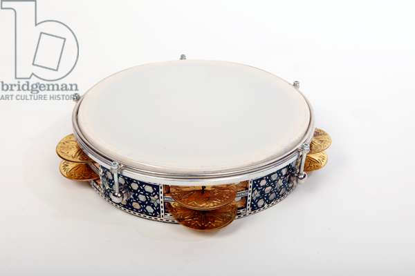 Riq, or Riqq, Egyptian Tambourine held vertically in one hand, and played by striking the skin with the other hand, as well as playing the heavy jingles with the fingers of both hands. Arabic. Generic