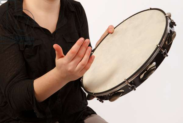 Pandeiro Tambourine in playing position. Held in one hand and played with the thumb and fingers of the other hand. Technique and striking positions.