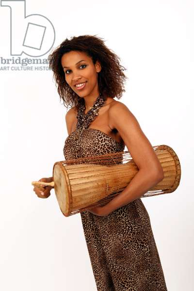 Young African woman playing a talking drum. An African  percussion instrument made from wodd and natural hide or skin. The drum is squeezed against the side of the player by the arm, whilst being struck with the curved stick, altering the tension on the s