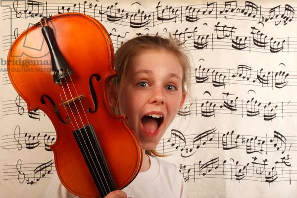 Young girl holding a violin in front from printed music.  The discovery of music in children. Music and youth. Surprised amazed.