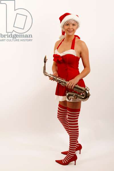 Young woman in a Miss Santa outfit holding an Alto Saxophone.