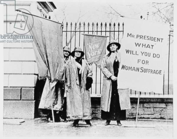 Women standing holding banners outside the White House Gate, Washington D.C. (b/w photo)