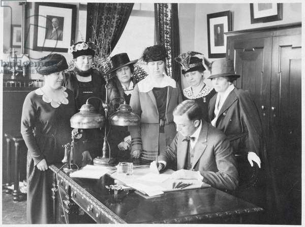Governor Carl Elias Milliken signing the Suffrage Bill as six women look on, 1917 (b/w photo)