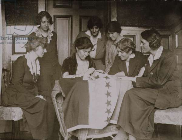 Alice Paul sewing stars on the suffrage flag as other women look on, c.1920 (b/w photo)