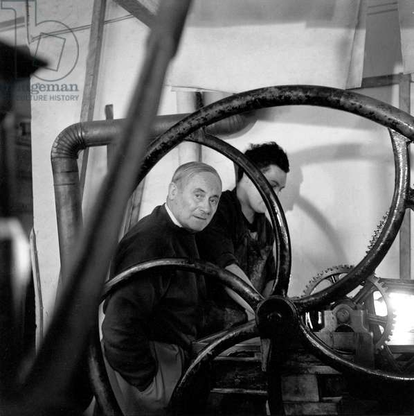 Joan Miro in the workshop of the Crommelynck Brothers in Paris watching a press, 1957 (b/w photo)