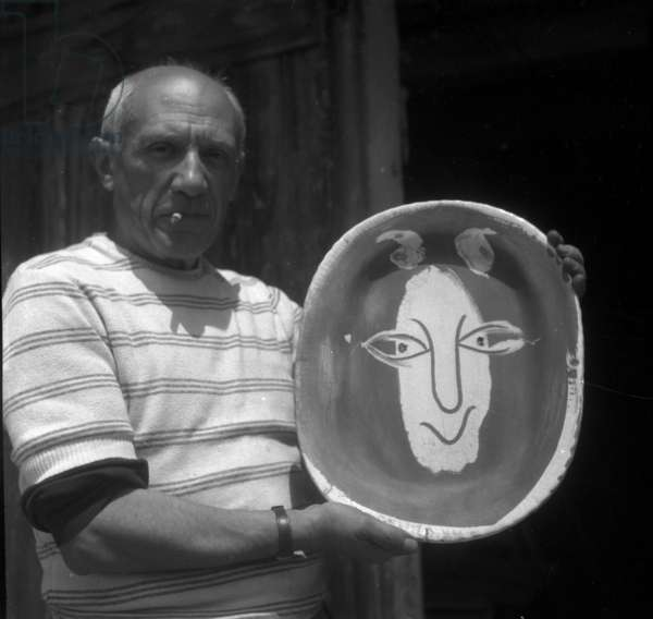 Pablo Picasso with a portrait of Henri Matisse at Madoura pottery workshop in Vallauris in 1948 (b/w photo)
