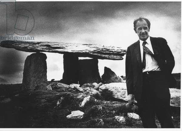 Sidney Nolan RA visits Poulnabrone dolmen at The Burren, County Clare, Ireland, in 1971 (b/w photo)