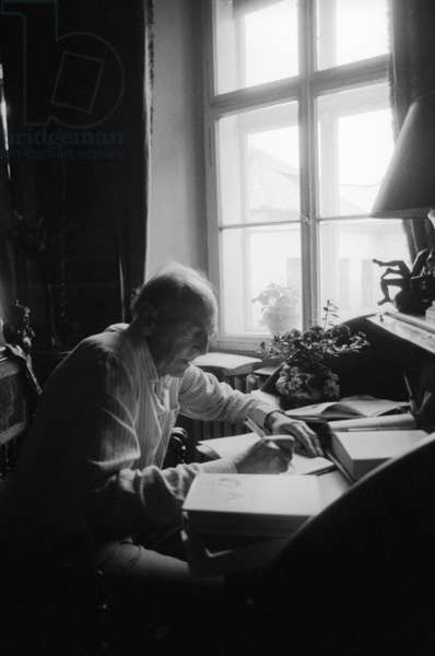 Jiri Mucha sitting at his desk in his house in Hradcany, Prague (b/w photo)