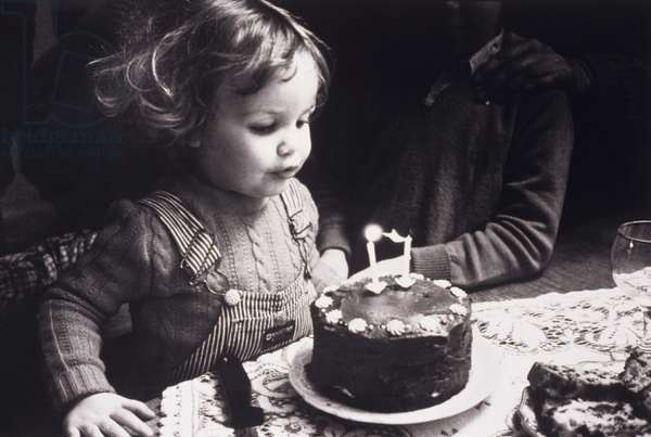Girl (2-3) blowing out candles on birthday cake